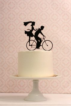 Who needs a fancy car when you can cycle off into the sunset? This cake topper with a bike silhouette by SilhouetteWeddings is beyond adorable.