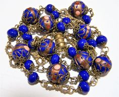 Vintage Mid Century Venetian art glass beaded necklace Blue wedding cake beads bordered by round blue beads and decorative gold tone knotted rope links Connected by decorative metal link connectors Screw barrel clasp 32 inches long Each glass bead is 5/8 diameter Good vintage condition, no cracks or other damage to the beads I specialize in vintage beaded jewelry, please visit my store for more offerings International buyers welcome, overcharges are refunded Priority shipping is optional...