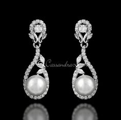 A single off-white pearl is held in a delicate design of round and marquise CZ crystals. Simple yet stunning these bridal earrings will add class to your wedding day. Also available in gold with ivory