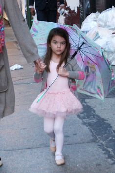 Suri Cruise's Best Fashion Moments, So Far At only 7, this little lady has donned more darling outfits than most of us could count in kindergarten. . . . Prima Ballerina - Who says tutus are only for dance class?  Four-year-old Suri takes her leotard to the streets and fancies it up with a corresponding gray cardigan and pretty parasol.