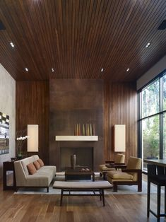 A modern and inviting space that combines glass, wood, and what looks like a concrete wall (at left).