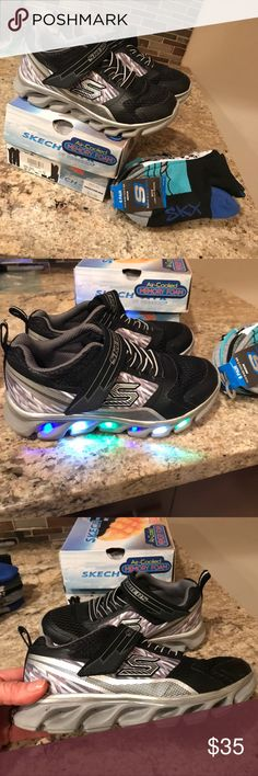 """Skechers light up sneakers boys size 12 & socks Super cute Skechers boys light up sneakers. Size 12  Bought this past December at sketchers store and wore on vacation.   ( bought 12 & 12.5 at time ) now after a month my son likes the bigger ones better🤭😌! (Of course that always seem to happen lol) also included 6 pack of Skechers skx sporty detailed socks shoe size 9.5-size 3 which I got on sale in the store for 11.00 for the 6 pack! They are low rise socks and your little """"big """" boy with…"""