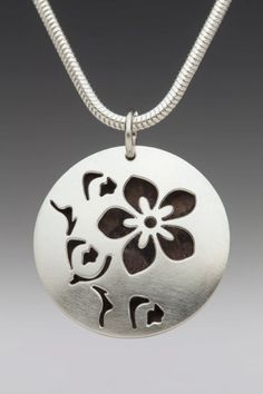 "Domed Hollow Round Oxidized Cherry Blossom Necklace.  The necklace is made of sterling silver, domed, hollow, round disks which are 1 1/4"" in diameter. They are pierced with a design of cherry blossoms and oxidized inside the hollow form to make the design stand out using contrast. The chain is also made of sterling silver."
