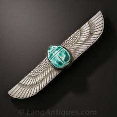 An ancient Egyptian scarab is set into a striking hand-engraved sterling silver wing pin - circa 1920s. The discovery of King Tutankhamen's tomb in 1922 inspired a craze for Egyptian motifs during the Art Deco period. This exotic jewel boasts a 2 1/2 inch wingspan.