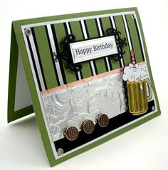 This birthday card was made for my Son in law. The color scheme is olive green and black with silver and copper foil accents. I added some old buttons, old grommets and a hand colored mug of beer for texture … Continue reading →