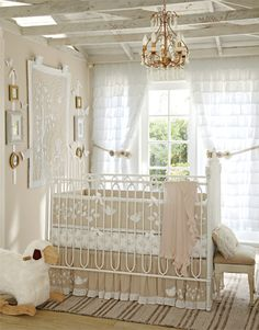 A warm beige on the walls and a distressed finish on the open-beam ceiling set the stage for a nursery that looks like a collection of vintage treasures. The ornate cast-iron crib, gold chandelier, and hand-stitched quilt displayed on the wall all have the look of prized antiques. We flanked the quilt with photo displays that add personality, and chose sweet, simple crib bedding with a timeless bird-and-branch motif.