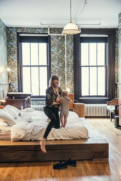Bedroom with wooden platform bed and botanical wallpaper