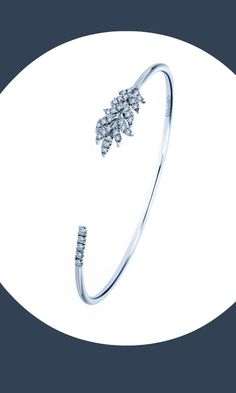 Let your imagination take flight with this feather motif cuff. The silver feather bracelet is adorned with white sapphires.