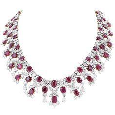 This stunning platinum and 18 karat yellow gold set necklace featuring 67 oval cut C. Dunaigre certified natural Burma rubies, weighing 110.23 carats. The rubies are adorned with 72.80 carats of marquise, pear shaped and round brilliant cut diamonds. 16.5 Inches long.