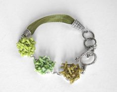 """$34 In four different hues of greens from Lime to Olive, this bracelet goes with everything green in your closet. The """"loose ends"""" are made of waxed cotton cording that I tie securely to a bezel base and soak with starch to keep their shape but retain their fabric texture. The ribbon is four layers of an olive colored organza in soft polyester."""
