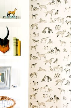 Dog wallpaper and white bookshelf in child's room