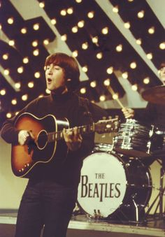 John Lennon with his second Gibson J-160E acoustic guitar, (a 1964 model), before he had the sunburst finish stripped. His original 1962 J-160E was stolen after a 1963 Christmas show at London's Finsbury Park Astoria Theatre.