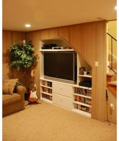 Utilizing dead space under stairs bespoke for Tv showcase designs under staircase