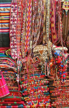 Peruvian textiles probably at Pisac market.Assortments like this are probably sold by  merchants who tend to exploit, the people. The belts look authentic, made by Inca villagers today but the weavers probably received little return. Some of the mantas (see left) are made with synthetic yarns, some even in factories. Better to buy the finest naturally-dyed textiles made by weavers associated with The Center for Traditional Textiles of Cusco, its museum & gift shop is at 603 Av Sol, Cusco.