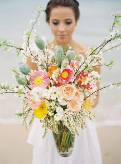 Sprawling branches, andromeda bunches, exotic fruits, garden roses, and ombré poppies transformed this arrangement into a destination wedding-ready bouquet.