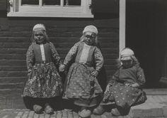 Drie jongetjes in Marker streekdracht. De jongens zijn gekleed in rokkendracht. Ze zijn als jongen ondermeer herkenbaar aan hun gebloemde schort en de witte strook in hun borstlap. Het zittende jongetje is in de rouw. 1943 #NoordHolland #Marken