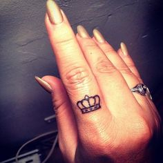 two small crown finger tattoos on one hand