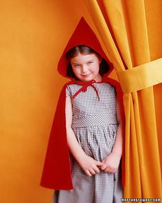 Our coy heroine wears a gingham party dress beneath her red corduroy  cloak, which happens to be pretty enough to wear year-round as a dressy  wrap.