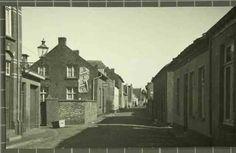 """Beschrijving: """"Hogesteenweg"""" doorkijk met links een uithangbord """"kapper"""", gezien vanuit de Beekstraat Locatie: Morregat; Hogesteenweg; Parochie Sint Martinus (Centrum); Weert;   Datering: 1937 - 1937"""