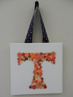Bright orange button monogram T on 10 inch by 10 inch square canvas, deep blue and orange polkadot ribbon hanger. Vintage and new buttons in all