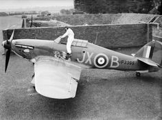 """P/O Arthur V """"Darky"""" Clowes of No 1 Squadron RAF climbs into Hurricane Mk I JX-B in a revetment at RAF Wittering in early October 1940. The aircraft was issued to the squadron upon its return from France in mid-June 1940 and taken on by Clowes near the end of August. Flying the aircraft, he claimed 2 destroyed, 3 probables and 2 damaged from his total score of 10½ destroyed, 3½ probables and 2 damaged."""
