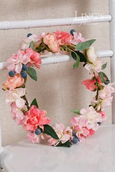 This beautiful is made of real-looking flowers: ivory and peach ranunculus, blush pink and coral violet and blue berries with green leaves. The
