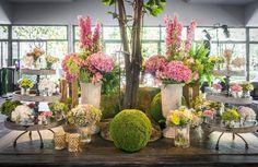 Trasera bodegón mesa hall, base de musgo con jarrones de flores, cajas de madera y velas. El Campillo + Mar de Flores