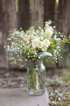 cream spray rose, Gypsophilia (babies breath), dusty miller (grey leaves), spirea (green leafy foliage with tiny white flowers), seeded Eucalyptus (brown and green seed like stems), and pale pink stock.