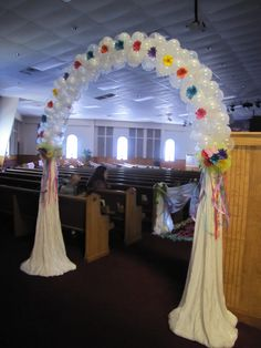 A balloon arch with draped side columns.
