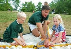 Brad Frey, who is gay and not allowed to be a Boy Scout leader, teaches Navigators Owen Russell and Gretchen Bush to put up a tent at a meeting at Mason's Pine Hills Park.
