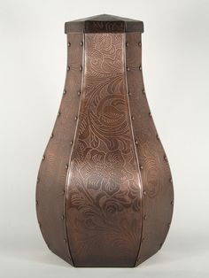 This urn is a customized version of the Toulouse design. The urn has flowing curves that give it an organic quality. It has a western leather tooling design etched onto the entire surface. This photo etched urn has a rich patina applied to it and than a coat of wax is applied to protect the finish. Find it at http://www.artisurn.com/collections/copper-urns/products/santa-fe-copper-urn. #copper #urn #handmade