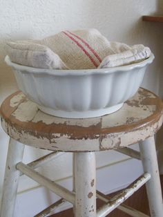 old stool. white bowl (ironware?), feed sack pillows. So stunning in it's simplicity. seen on Secret Garden Cottage.