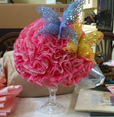 Styrofoam ball decorated with cupcake wrappers. Butterflies added to match theme.