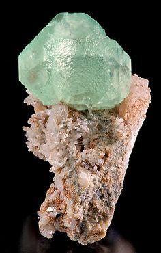 Fluorite octahedron atop Quartz covered matrix