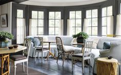 Jeffrey Bilhuber ~ In a Federalist-inspired stone house in Connecticut's Litchfield County, a graceful demilune banquette in front of the living room's grand bay window. One of the marquetry-detailed tilt-top tables in front of it is period, the other a faux bois painted replica.