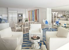 Here's a unique take on the zebra print rug with a blue and white zebra print rug in a predominantly white living room containing 4 white slip-covered armchairs and a small round white coffee table in a large open concept living space that contains another small living room area, kitchen and dining area