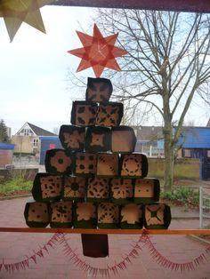 Map juf Ineke: raamdecoratie. Kinderen vouwen een bakje van zestien vierkantjes, knippen een kleedje dat ze erin plakken.