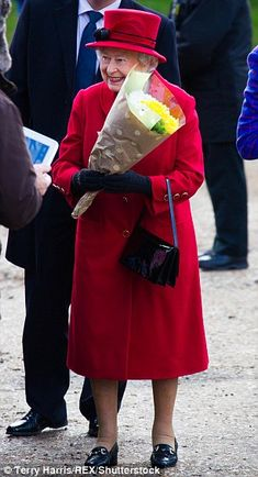 The Queen made a colourful entrance to the church in a bright red coat with matching hat