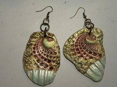 Seashell stamped polymer clay earrings finished in metallic paints and pigments.