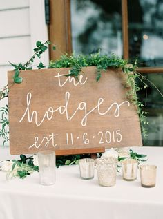 Wooden wedding sign dripping with garland: http://www.stylemepretty.com/south-carolina-weddings/charleston/2016/09/08/charleston-outdoor-intimate-wedding-at-the-river-house/ Photography: Sarah Joelle - http://www.sarahjoellephotography.com/