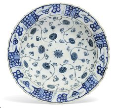 AN IZNIK BLUE AND WHITE POTTERY DISH   OTTOMAN TURKEY, SECOND HALF 16TH CENTURY   With cusped sloping rim on short foot, the white interior painted in two shades of blue, the central cusped roundel with blue-grey scrolling tendrils issuing flowerheads around a central rosette, the rim with cobalt-blue stylised wave and rock design, the exterior with alternating rosette and leaf designs