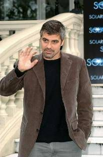 George Clooney knows how to wear a casual outfit well. Grey cotton trousers with a black crew neck sweater and brown mohair sport coat is a timeless look without being boring