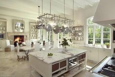 J.Eckert Photography  ~large, open chic kitchen design with stainless steel pot rack, white kitchen cabinets, marble countertops, kitchen island, marble floors and fireplace.
