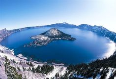 The whiteness of winter meets the deep blue of Crater Lake  (© Francois Gohier/Ardea/Caters News)
