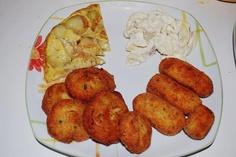 potato-based dinner: potato omelette, zucchini and carrot patty, bacon croquettes, yogurt and potato salad