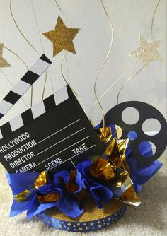 This centerpiece makes a great table decoration for any Hollywood Movie Theme Party, Award Banquet, Bar Mitzvah, Corporate Event, Fundraiser and more! This centerpiece on a 8 base with regular and foil tissue paper poufs, glittered stars curly ting ting and base ribbon trim. Also
