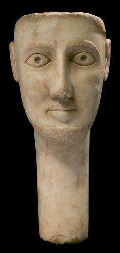 STÈLE ICONIQUE. Elle représente le visage d'un homme de face, juché sur un long cou, le nez triangulaire surmontant une fine bouche. Les yeux sont surmontés d'arcades sourcilières marquées. La barbe et la moustache sont figurées. La coiffure, probablement en stuc, était rapportée. Albâtre. Péninsule sudarabique, ca. IIe-Ier siècles av. J.-C.