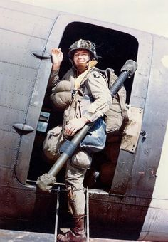 US 101st Airborne Division paratrooper Corporal Louis E. Laird, carrying bazooka, boards a C-47 transport during dress rehearsals for the Normandy invasion, spring 1944.