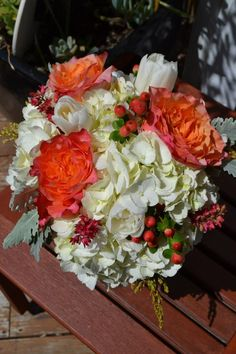Chic white and orange bridal bouquet with hydrangea, roses, tulips, and hypericum berries. Fleurish Floral Designs