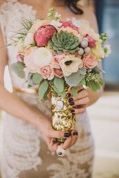 For rustic wedding style, carry a bridal bouquet full of texture and various plants and florals. Featuring cotton, berries, branches and succulents, this arrangement blends both modern and boho wedding styles. The pink peonies and blush garden roses add a feminine touch.